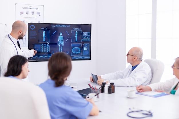 전문 의사가 프레젠테이션을 하는 동안 의료진이 회의실의 책상에 앉아 있습니다.