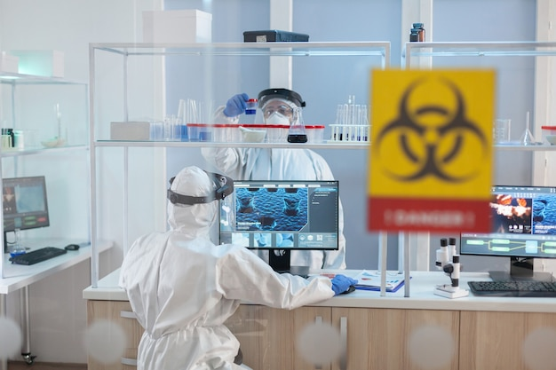 Medical staff wearing ppe suit in laboratory danger zone during pandemic. group of doctors examining vaccine evolution using high tech for diagnosis against covid19.