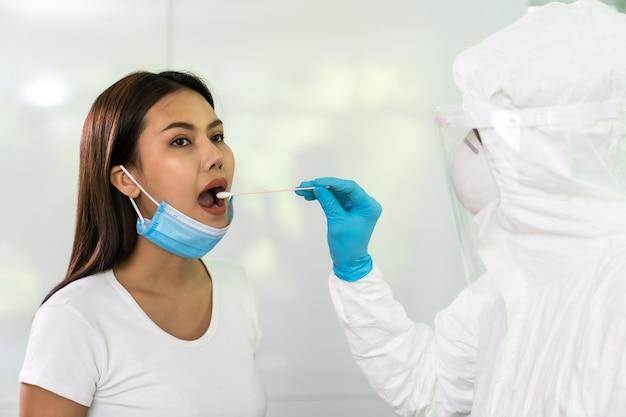 Ppeスーツの医療スタッフが自宅の喉綿棒でアジアの女性にコロナウイルスcovid-19をテストします。在宅での新しい通常のヘルスケアサービス、医療サービス、covid-19テストのコンセプト。