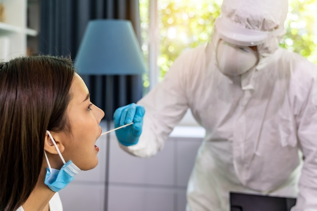 Ppeスーツの医療スタッフが自宅の喉綿棒でアジアの女性にコロナウイルスcovid-19をテストします。自宅での通常の新しいヘルスケアサービスと医療配達の概念。