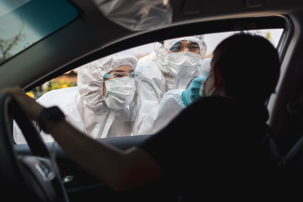 Medical staffs with ppe use infrared thermometer gun to check body temperature at drive thru station in hospital. new normal healthcare and medical concept.