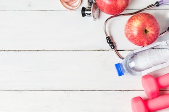 Medical stethoscope and an apple fruit over wooden background. Healthy lifestyle concept image.