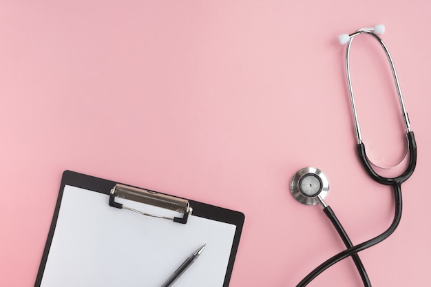 医療聴診器とピンクのテーブルに空のクリップボード