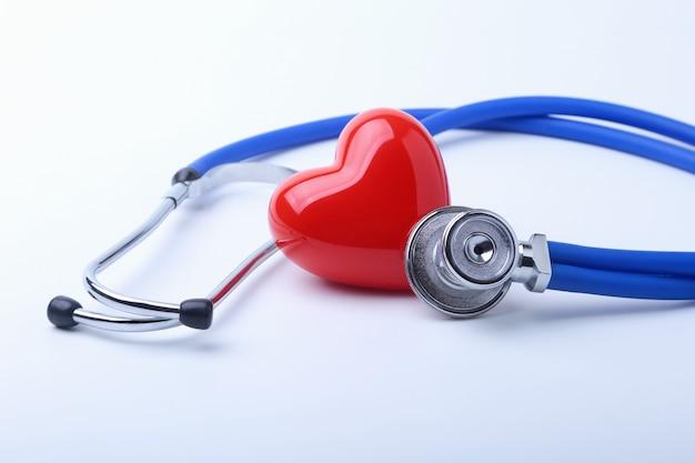 Медицинский стетоскоп и красное сердце изолированные на белизне.