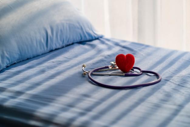 医学の聴診器と患者のベッドの上の赤いハート