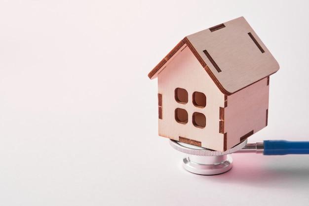 コピースペースとピンクの背景に医療聴診器とおもちゃの家
