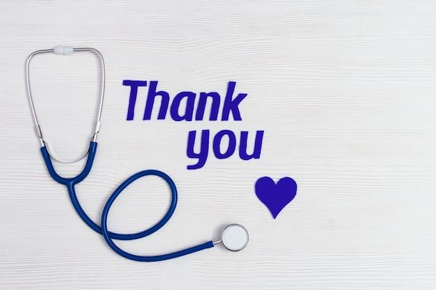 医学の聴診器、青いハートとコピースペースと白い木製の背景に「ありがとう」のテキスト。ヘルスケア医学の概念。国民看護師の日。