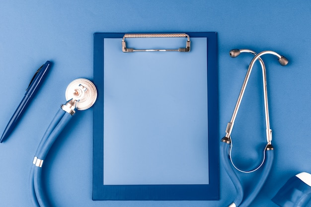 Medical stethoscope and clipboard on classic blue color, top view