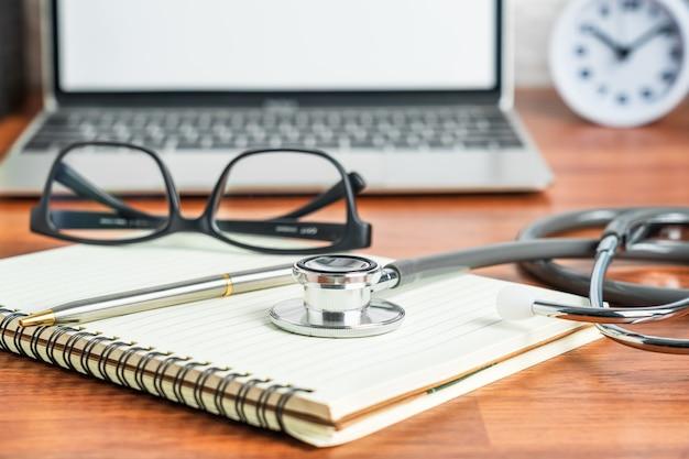 医療概念として医師のメモ帳にラップトップコンピューターを使用して医師の健康診断のための医療聴診器