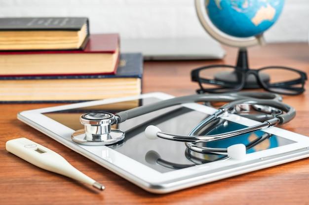 医療コンセプトとして医者のテーブルにタブレットコンピューターで医者の診断のための医学の聴診器