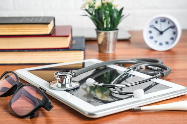 医療概念としての医師のテーブル上のタブレットコンピューターによる医師の健康診断のための医療聴診器