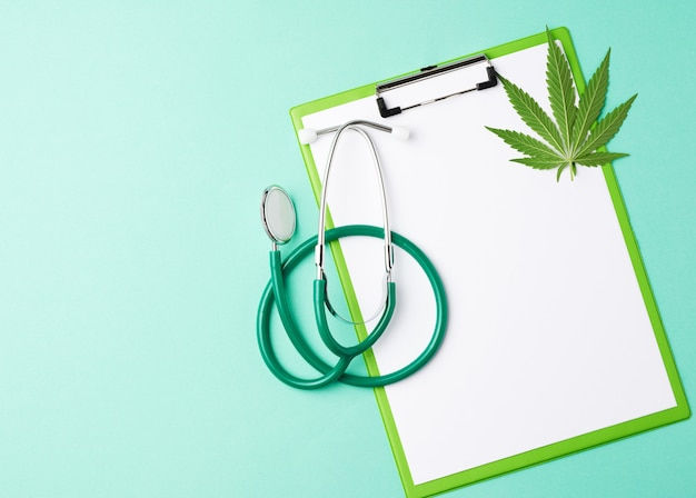 Medical stethoscope and green hemp leaf on a green space, top view