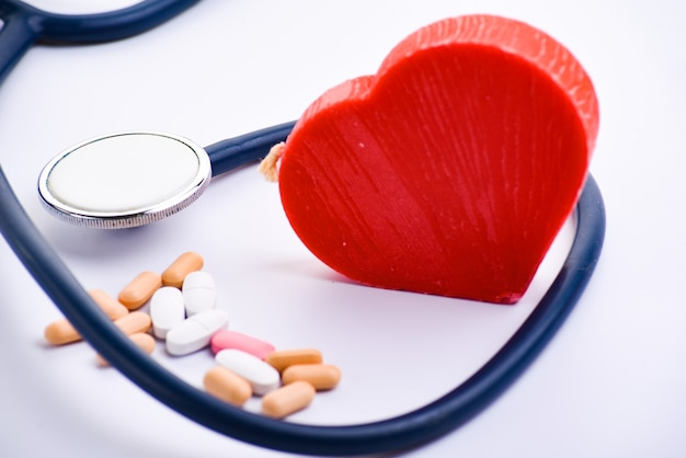 Medical stethoscope, pills and red heart. cardiology concept