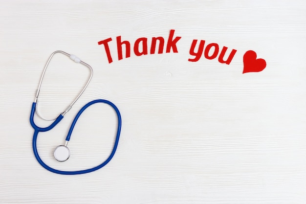 Medical stethoscope, red heart and thank you text