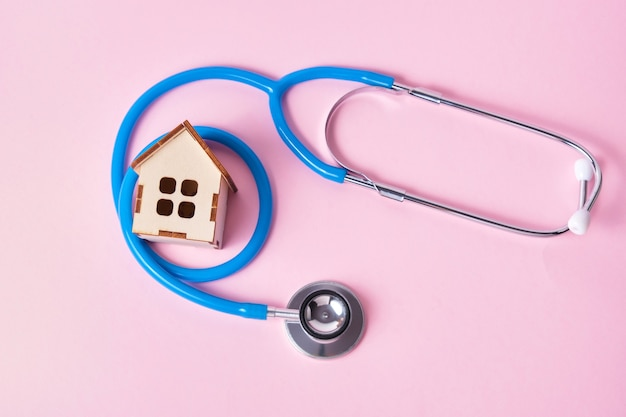 Medical stethoscope and toy house on a pink surface with copy space