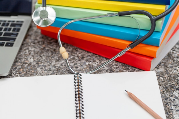 Medical stethoscope with notepad and books on desk, medical concept.