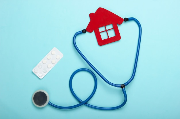 Medical still life. stethoscope, figurine of the hospital house, pills on blue background. flat lay