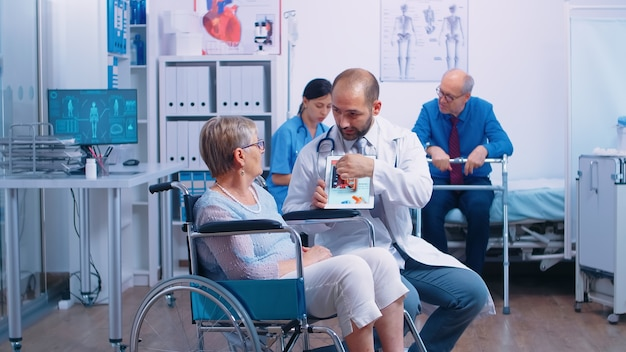Medical stuff presenting a booklet with arrhythmias and other heart related disease to senior woman in wheelchair into a recovery clininc. health care, medical advice and rehabilitation