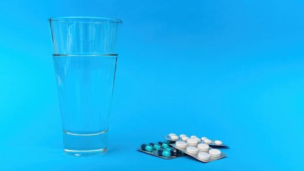 파란색 배경에 의료 용품 및 항목 구성입니다. 물 한잔과 함께 알약 팩의 스택