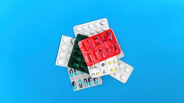 Медицинские принадлежности и состав предметов на синей поверхности. стек упаковок таблеток. вид сверху