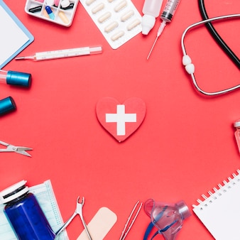Medical supplies around heart with cross