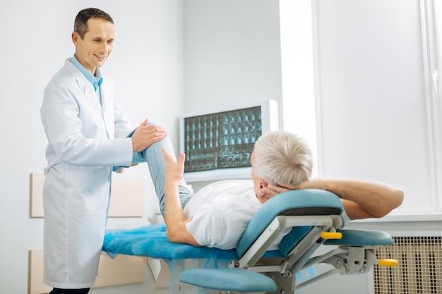 Медицинское сопровождение. счастливый положительный мужчина-врач держит ногу пациента и улыбается, оказывая ему медицинскую поддержку