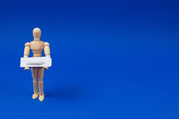 Medical suppository, rectal or vaginal. wooden man holds medical suppository on blue background.