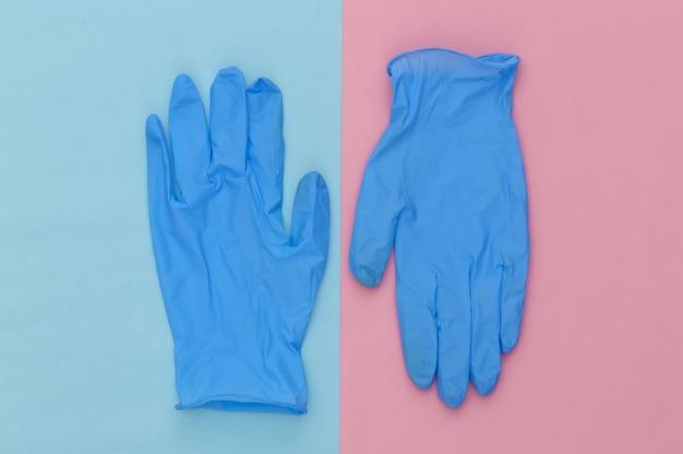 블루 핑크 파스텔 배경에 의료 수술 장갑. 평면도