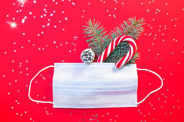 Medical surgical protective mask with christmas tree branch and lollipop on red with silver stars. flat lay.