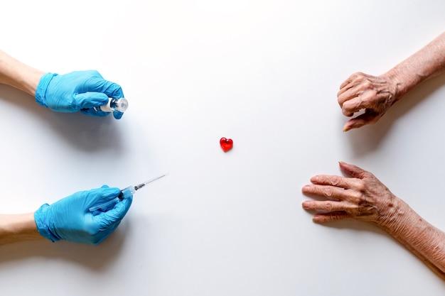 医療用手袋の医師の手に薬を入れた医療用注射器とアンプル