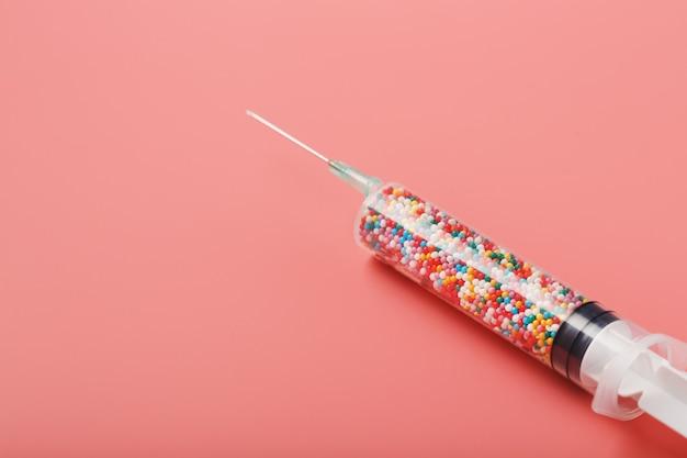 공간이 분홍색 배경에 다채로운 풍선 가득 의료 주사기. 개념적 의료 백신 개발.