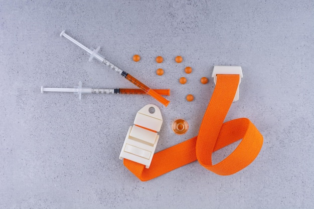 Medical syringe and tablets on marble background. high quality photo