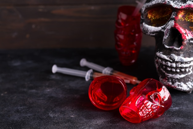 Medical syringes with tomato juice and a human skeleton face as cup on black