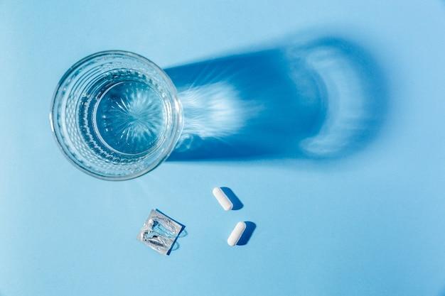 青い背景の上の水のガラスと医療タブレット