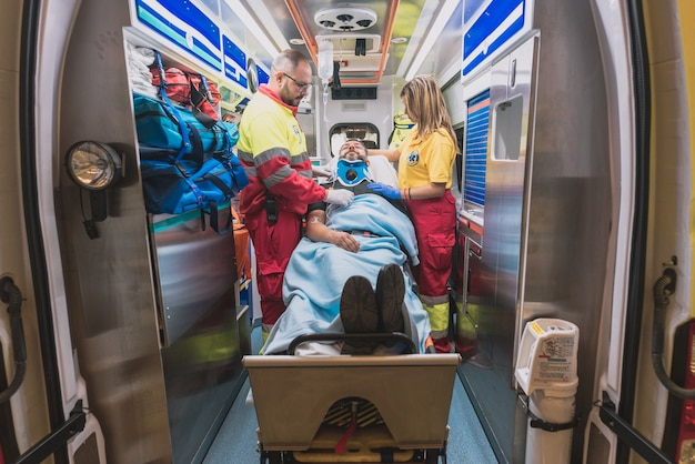 A medical team in an ambulance helps an adult man