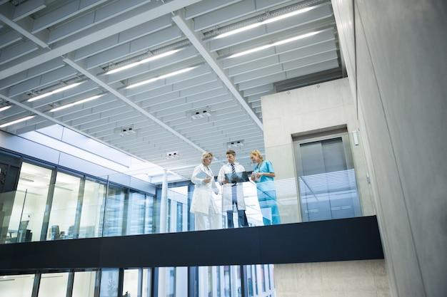 복도에서 엑스레이 보고서를 통해 논의하는 의료 팀