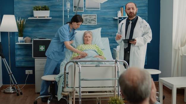 병원 침대에서 아픈 환자를 검사하는 의료 팀