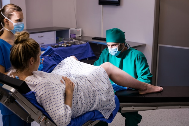 Medical team examining pregnant woman during delivery