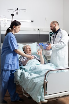 Medical team helping senior woman patient laying in hospital bed, to breath with espiratory mask with resuscitator for ventilation of patient, during cardiopulmonary resuscitation process.
