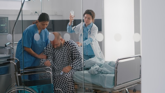 Equipe medica che aiuta il paziente malato con frattura alla gamba che si mette in sedia a rotelle