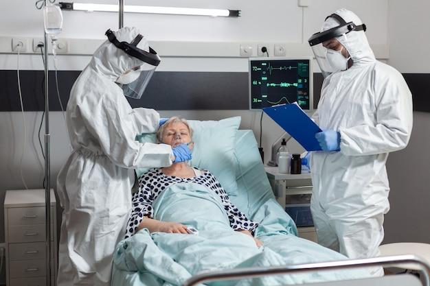 Медицинская бригада в клинике в комбинезоне ppe и защитной маске во время посещения пациента в больничной палате во время перерыва из-за коронавируса для предотвращения заражения