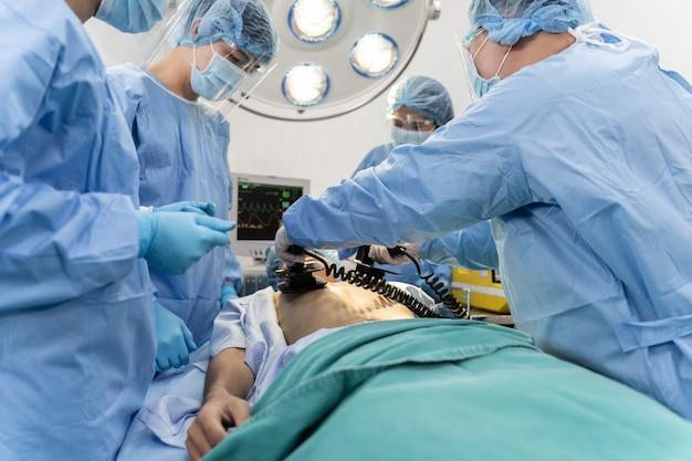 Медицинская бригада в хирургическом халате помогает пациенту сделать сердечно-легочную реанимацию cpr
