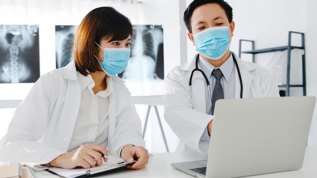 병원 사무실에서 컴퓨터 단층 촬영 결과를 논의하는 보호 얼굴 마스크와 아시아 심각한 남성과 젊은 여성 의사의 의료 팀.