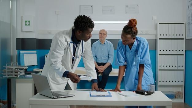 バックグラウンドでベッドに座っている高齢の患者との健康診断の予約のための機器を使用している人々の医療チーム。診断のために机の上にラップトップとドキュメントファイルを持っている医師と看護師