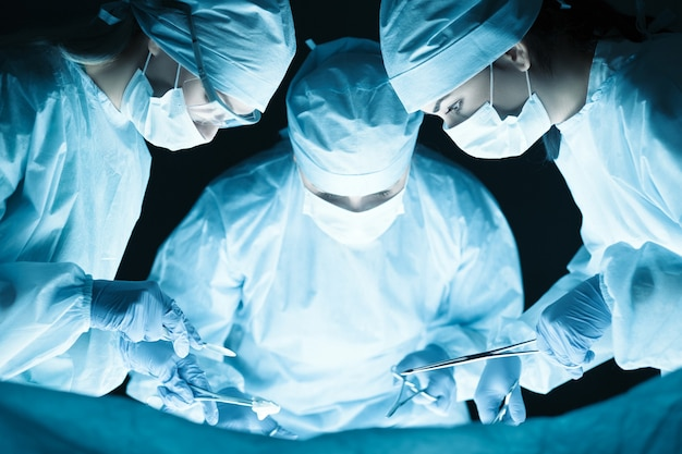 Medical team performing operation in operating theatre