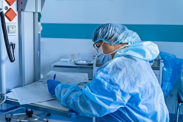 Медицинская бригада, выполняющая хирургическую операцию в яркой современной операционной. операционная. современное оборудование в клинике. приемный покой.