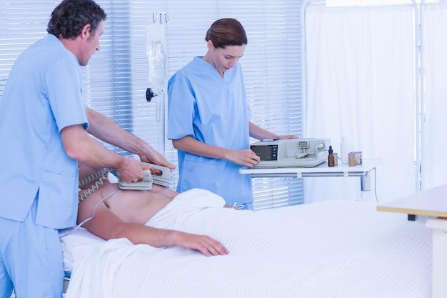 Medical team resuscitating a man with a defibrillator