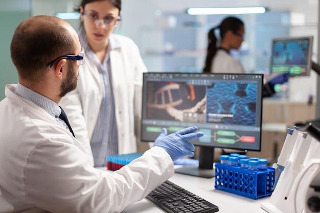 혈액 샘플로 테스트 튜브를 들고 컴퓨터에서 찾고 dna 실험을 수행하는 의료 팀 과학자