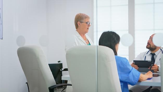 タブレットとクリップボードを使用して患者の文書を使用して、病院の会議室のテーブルに座って話し合う医療チーム。診療所で病気の症状について話している医師のグループ