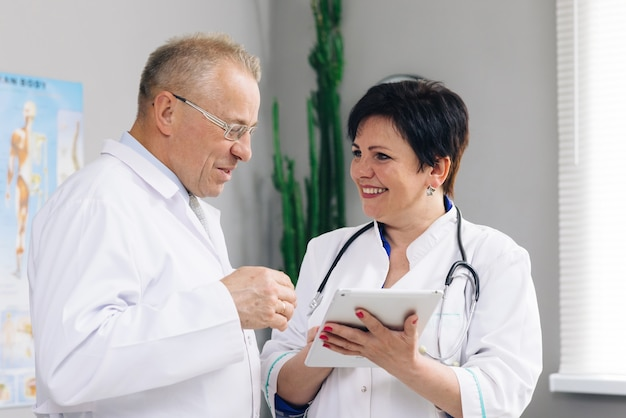 Medical team two old male and young female doctors wear white coats talk, use digital tablet